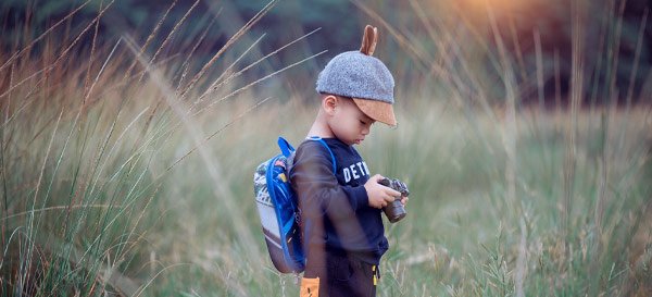 Toddler holding camera in field