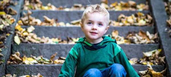 Boy sitting on leaf covered concrete stairs